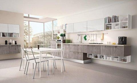 una cucina con mobili marroni e bianchi e un tavolo con delle sedie