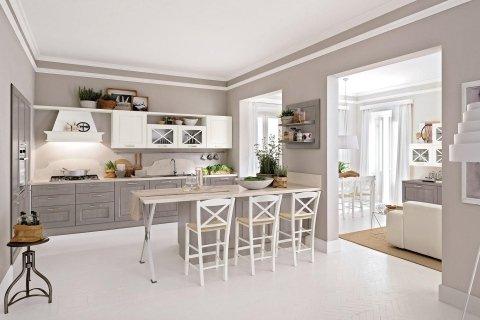 una cucina marrone e beige e un tavolo con delle sedie