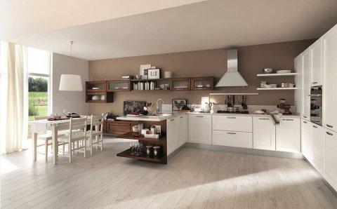 una cucina con mobili bianchi e marroni e un tavolo con delle sedie