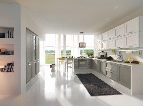 una cucina con mobili grigi e bianchi