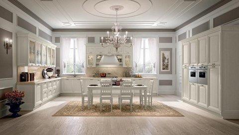 una cucina di color bianco e un tavolo al centro