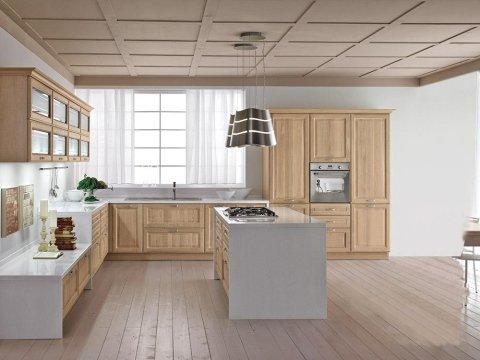 in cucina con penisola e mobili in legno chiaro