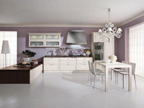 una cucina con mobili color panna e un tavolo con delle sedie