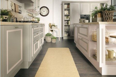 un tappeto giallo e una cucina con mobili verdi e bianchi