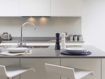 una cucina con mobili bianchi e marroni e un tavolo giallo con sedie grigie