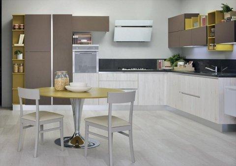 una cucina con mobili marroni, una poltrona nera e un tavolo con delle sedie