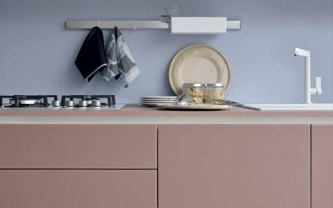 un mobile cucina di color rosa con piano cottura e lavandino