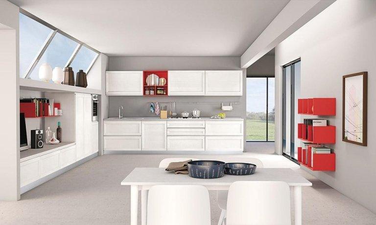 la cucina con mobili bianchi e rossi e un tavolo con delle sedie
