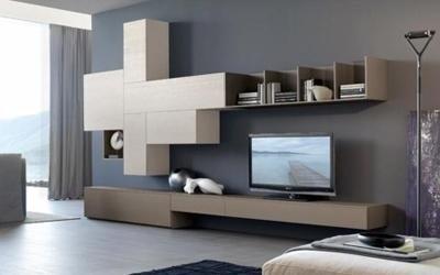 una libreria, un mobile color grigio e sopra una tv