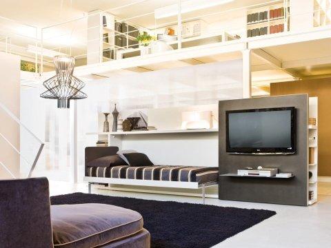 un letto singolo e una TV a muro su un pannello marrone