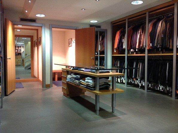 interno del negozio d'abbigliamento con un tavolo al centro e dei vestiti appesi a degli appendini