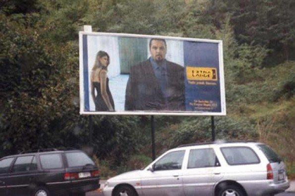 un cartello pubblicitario con scritto extra large e sotto delle macchine parcheggiate