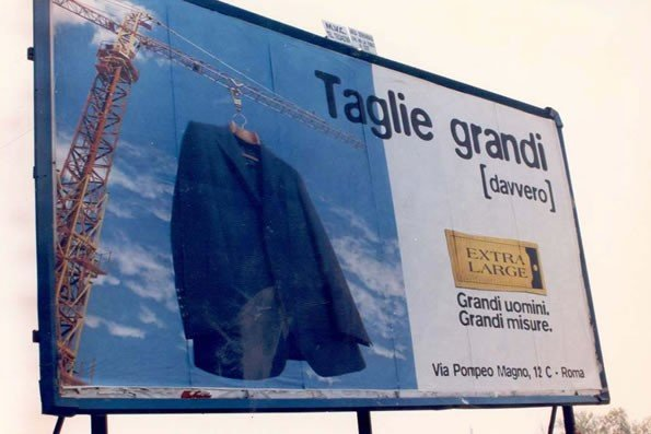 un cartello pubblicitario con una gru che solleva una giacca e la scritta taglie grandi