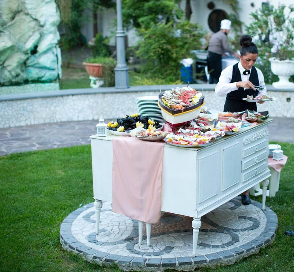 un cameriere di fronte a un tavolo da buffet imbandito