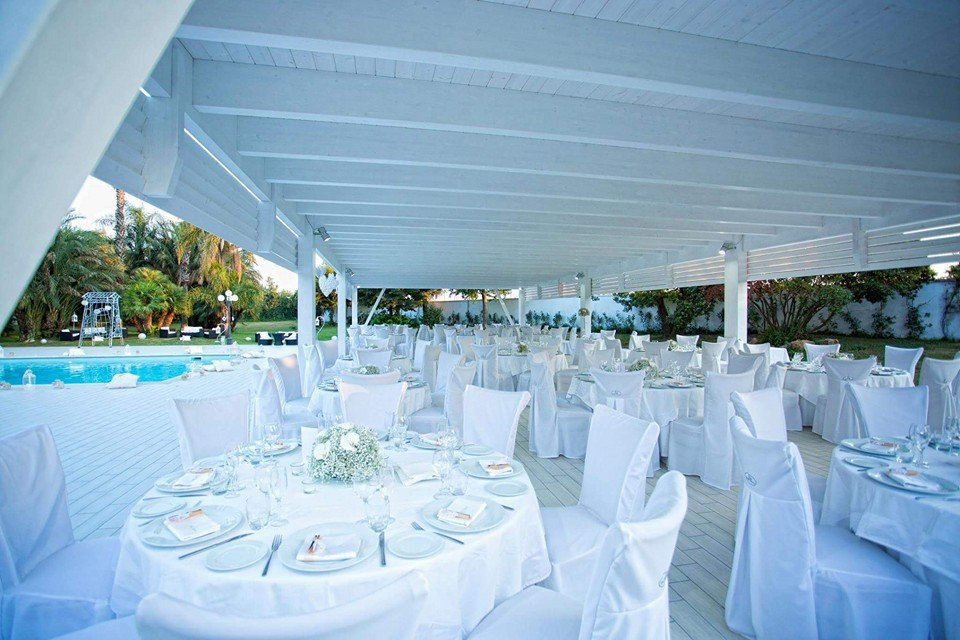 Tanti tavoli eleganti in bianco sotto una copertura esterna bianca