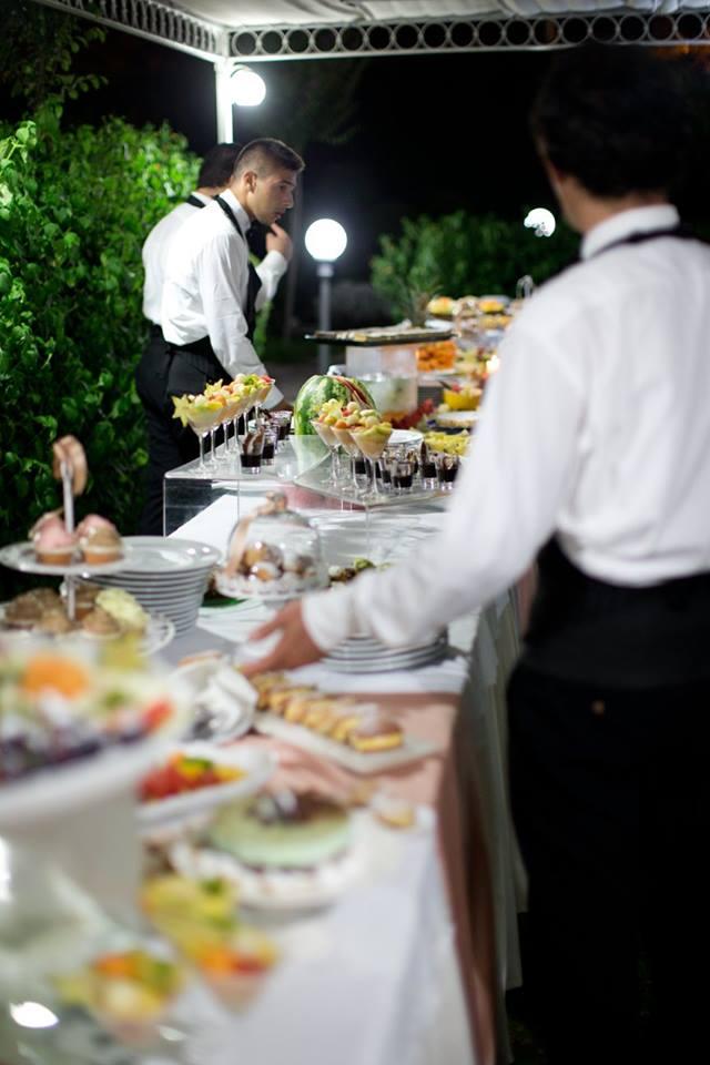 due camerieri preparano un tavolo da buffet