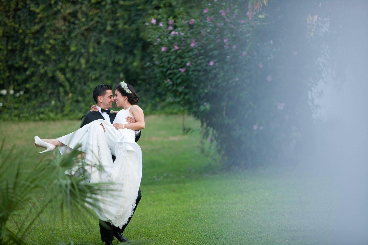 Uno sposo che porta in braccio una sposa in un giardino