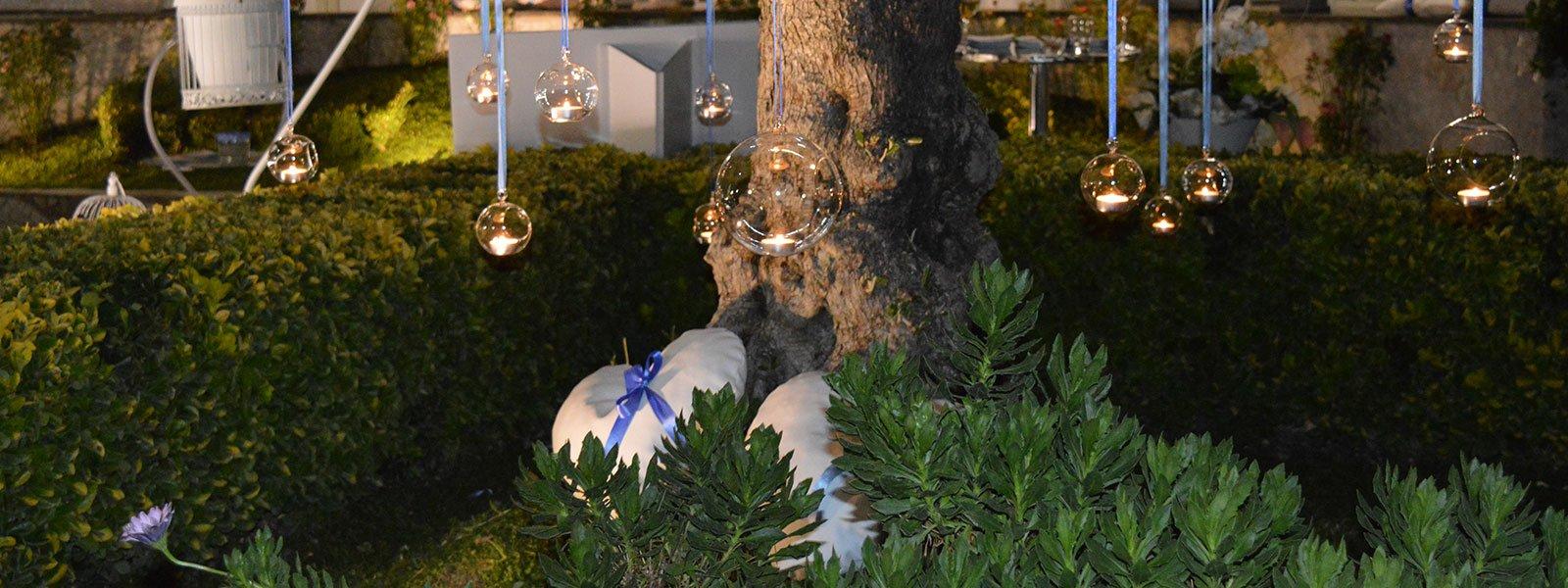Un albero con porta lumini di vetro appesi durante una serata