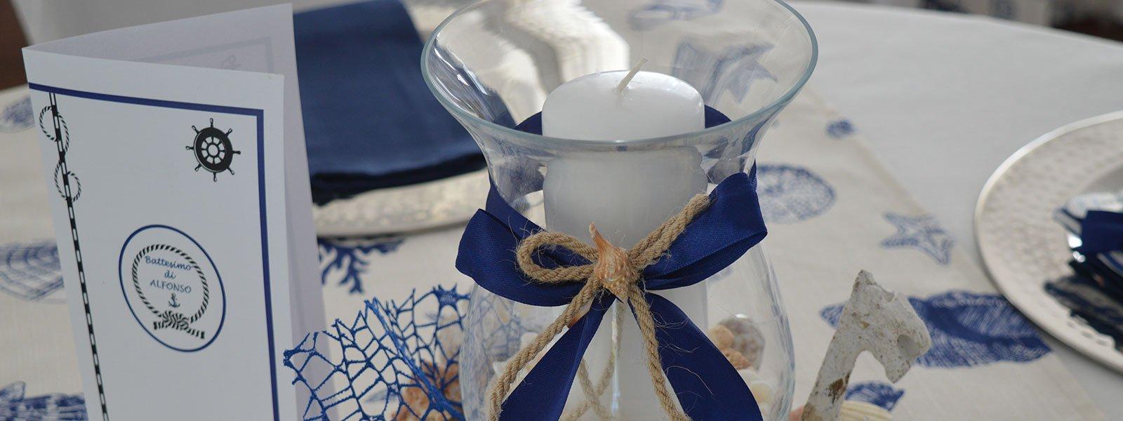 Un vaso con un fiocco di color blu, una candela bianca e accanto un invito con scritto battesimo di Alfonso