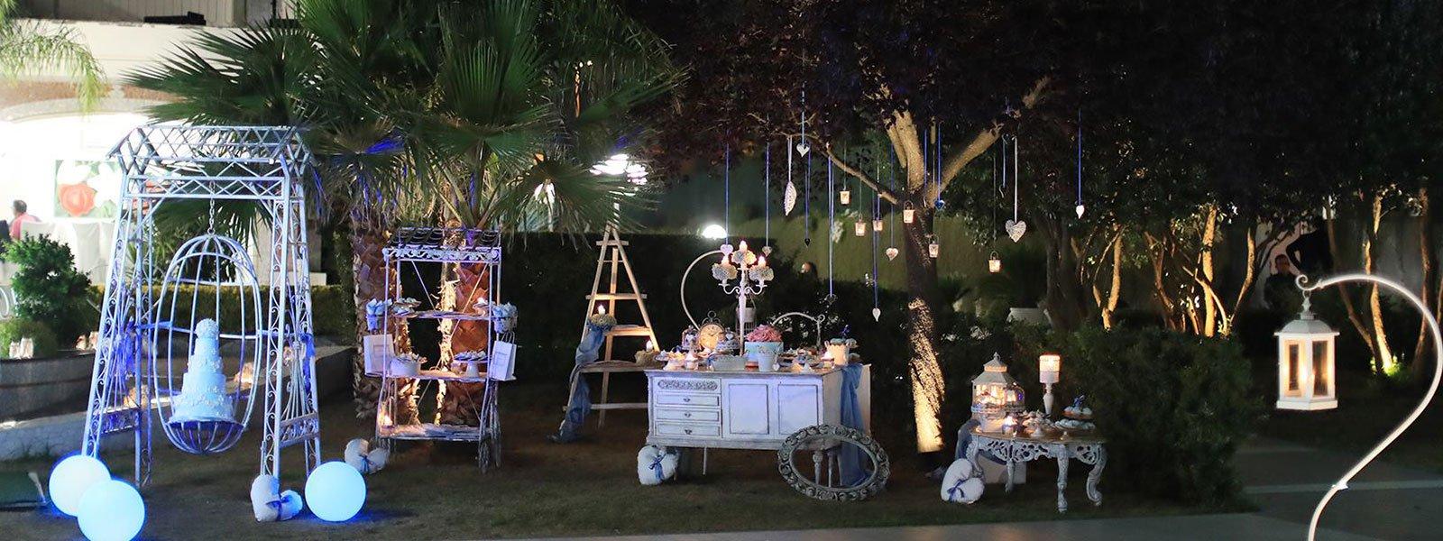 Un giardino con tavolini, stand con confetti e lumini a forma di cuore appesi su un albero