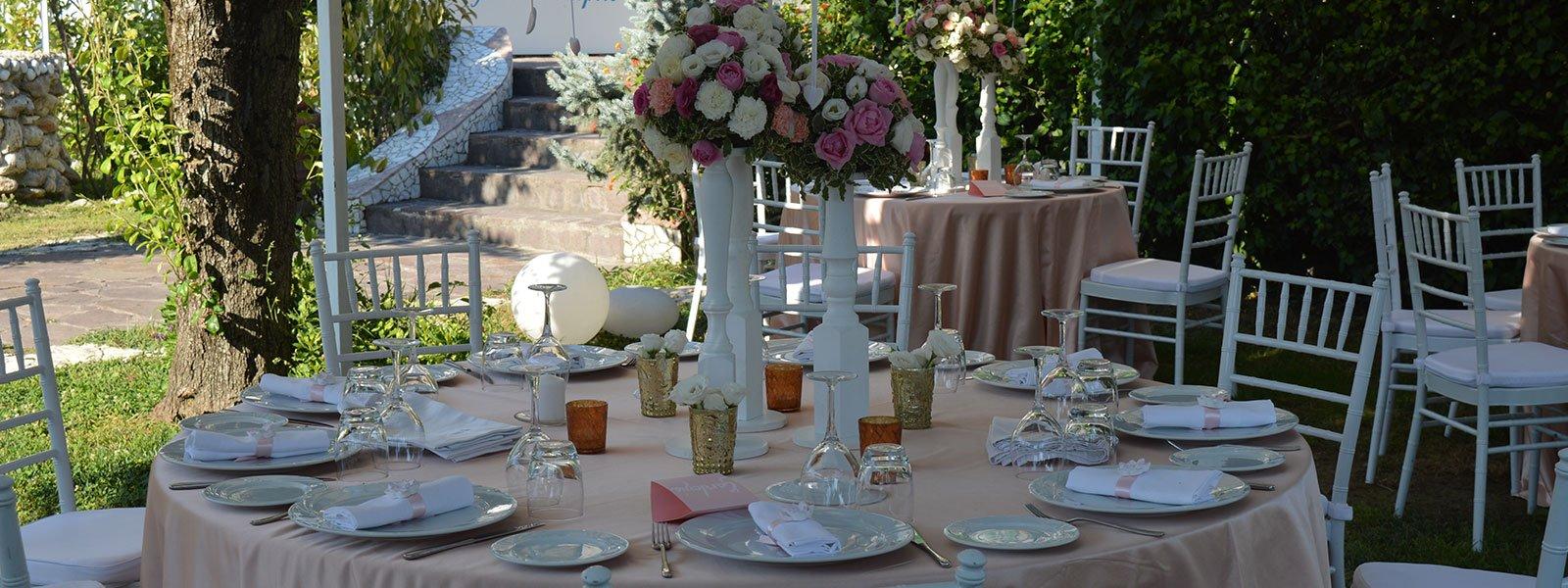 un tavolo apparecchiato per un ricevimento con un vaso di fiori bianchi e rosa al centro, accanto altri tavoli e dietro vista del giardino