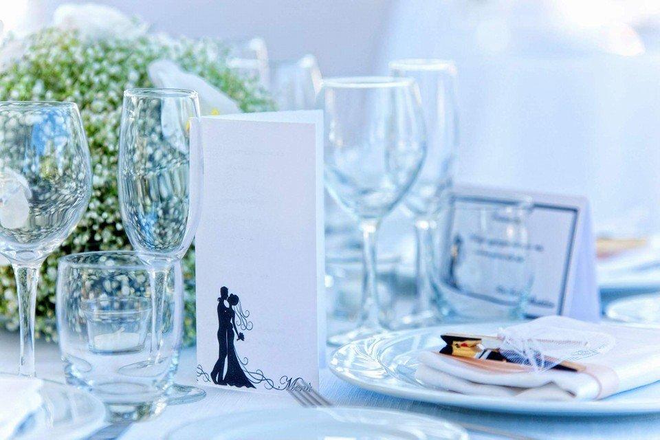 Un tavolo con bicchieri di vino, decorazioni di fiori al centro e un invito appoggiato con un'immagine di due sposi abbracciati