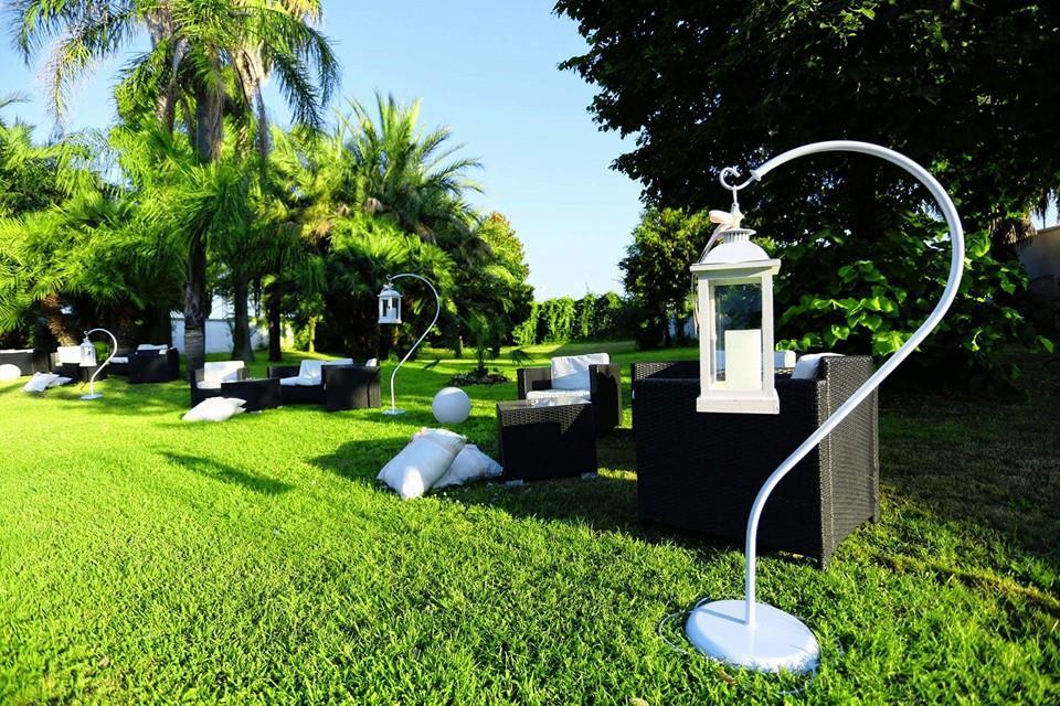 Poltrone da esterno, lampioni in un giardino con prato verde e delle palme
