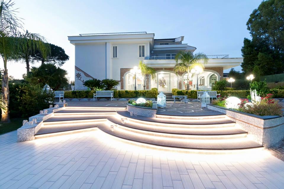 Una villa illuminata durante la sera e vista delle scale e alcune panchine