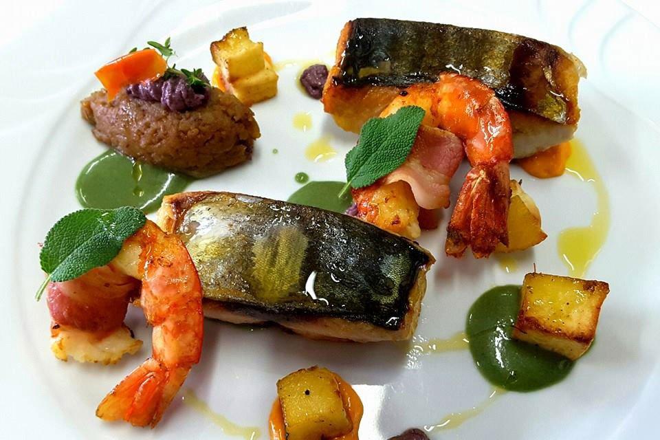 un piatto gourmet a base di pesce con gamberi, bistecche di pesce e delle salse
