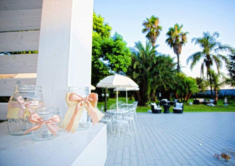 Vista di un giardino con palme, tavoli e sedie e alcuni barattoli con fiocchi appoggiati su un muro sulla destra