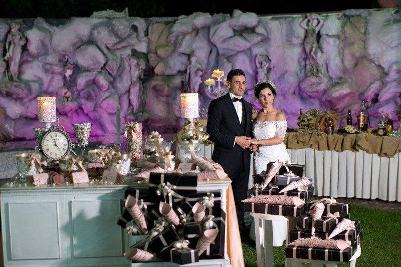 Una coppia che si tiene le mani, dei tavoli con confetti e decorazioni con lumini
