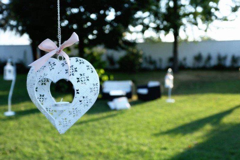 Vista ravvicinata di un porta lumino a forma di cuore appeso su un albero nel giardino