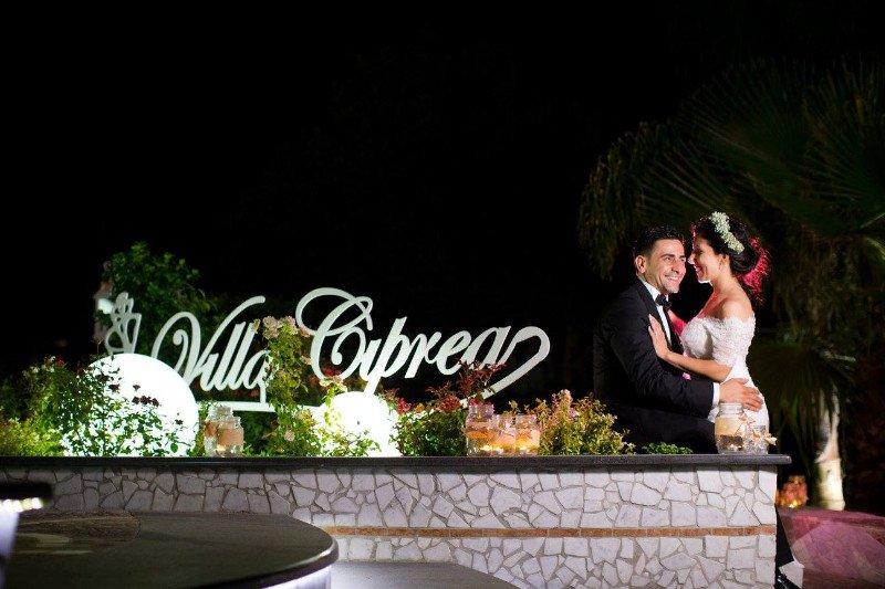 Una coppia mentre si abbraccia e sulla destra la scritta Villa Ciprea tra le piante e alcune lampade