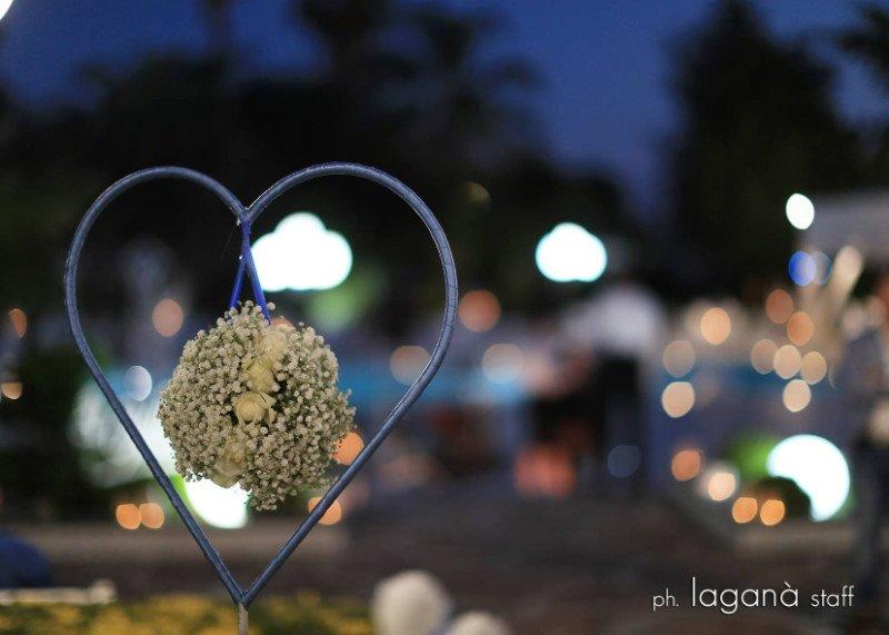 Un'immagine con vista ravvicinata di un cuoricino con dei fiori e roselline bianche appese e una scritta sotto ph Lagana' staff