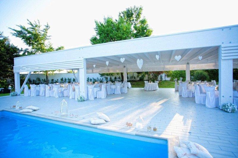 vista dei tavoli apparecchiati per un ricevimento sotto a una tettoia bianca in legno e dietro vista della piscina