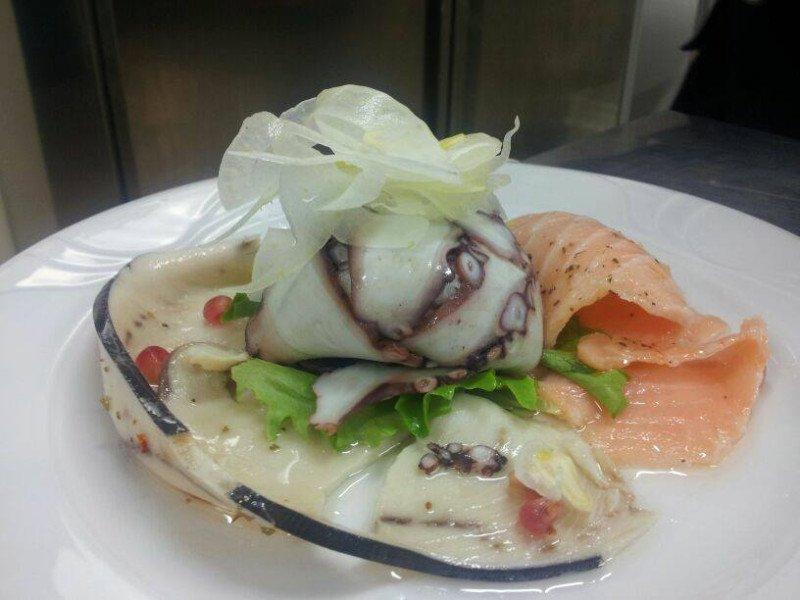 un piatto a base di pesce con salmone, polipo e altre specialità