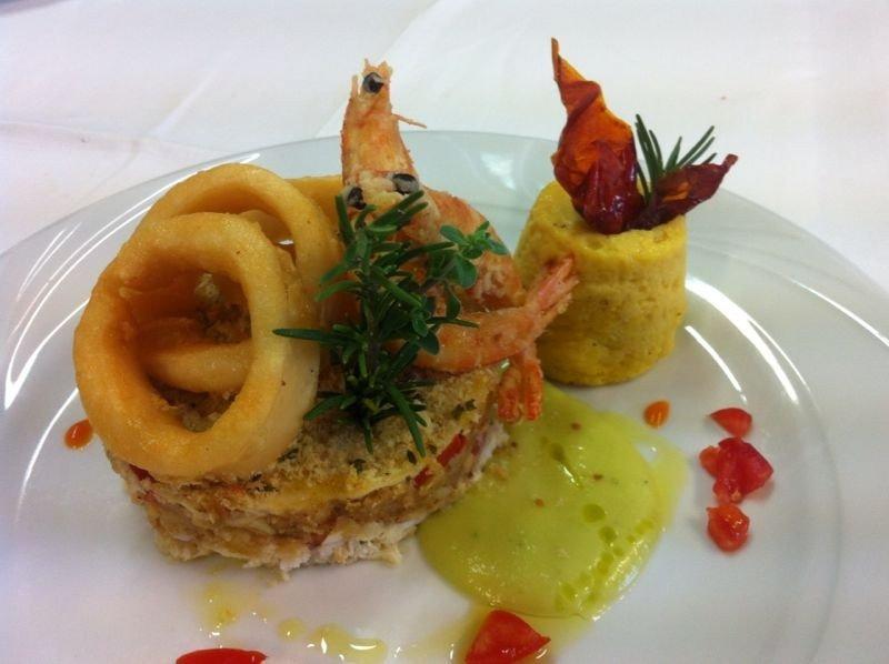 un tortino con sopra degli anelli di calamari, un gamberone e accanto del formaggio sciolto con un altro tortino con sopra  del peperoncino