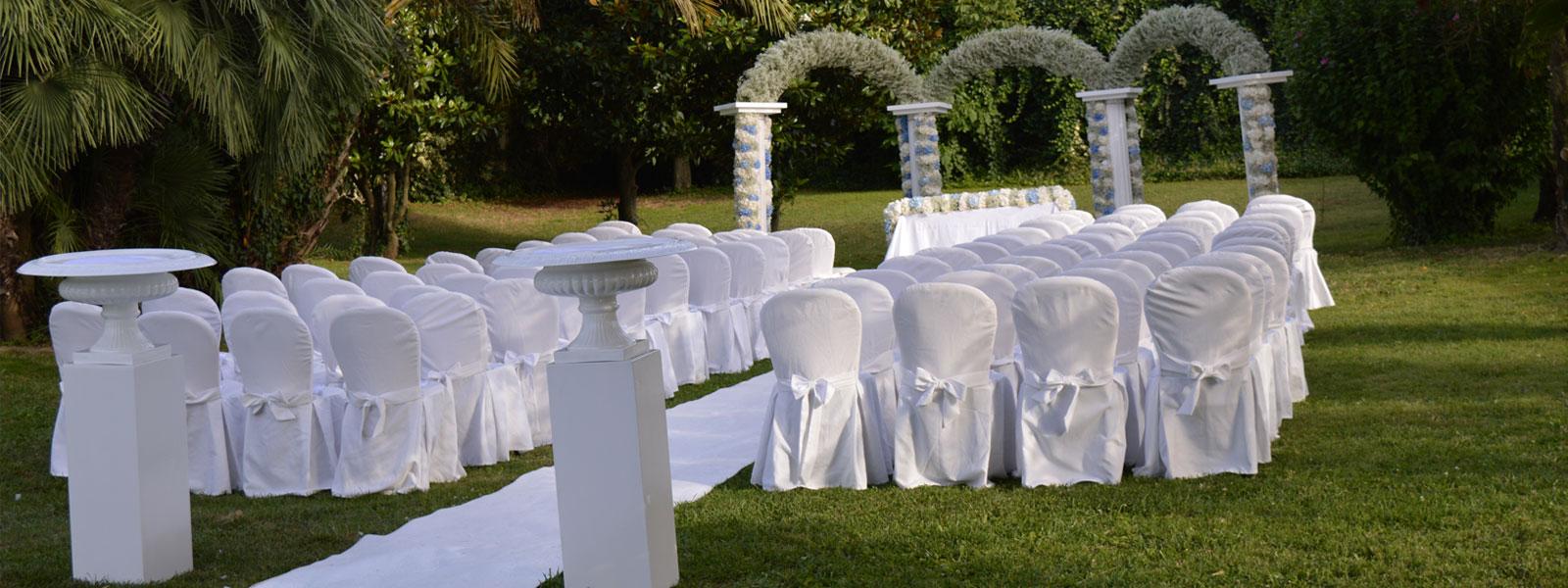 Un prato con delle sedie con copri sedie di color bianco un tappeto bianco e un tavolo con decorazioni con dei fiori