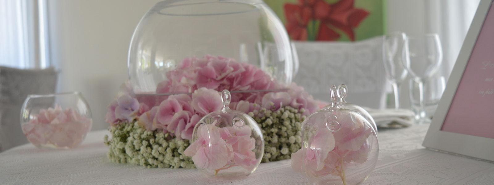 Un tavolo con bicchieri di vino e decorazione con dei fiori rosa dentro a dei vasi di cristallo