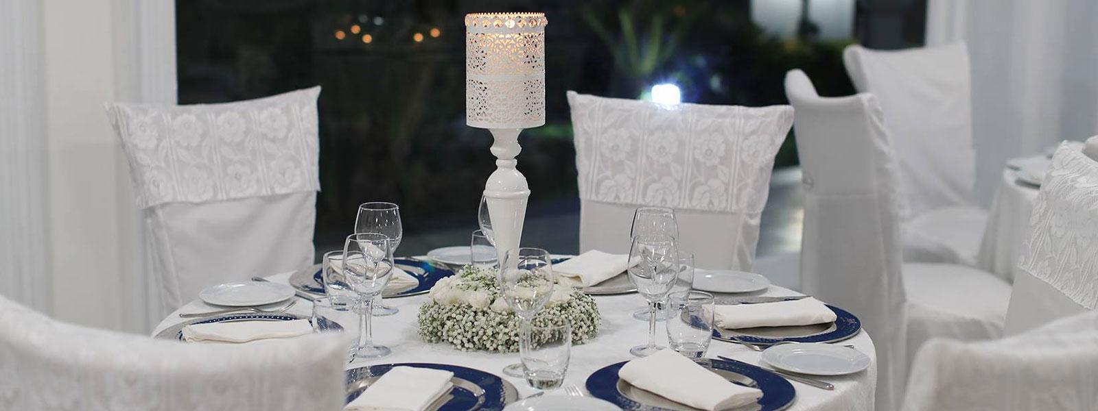 Tavoli apparecchiati con tovaglie bianche, un lumino e decorazione con dei fiori al centro