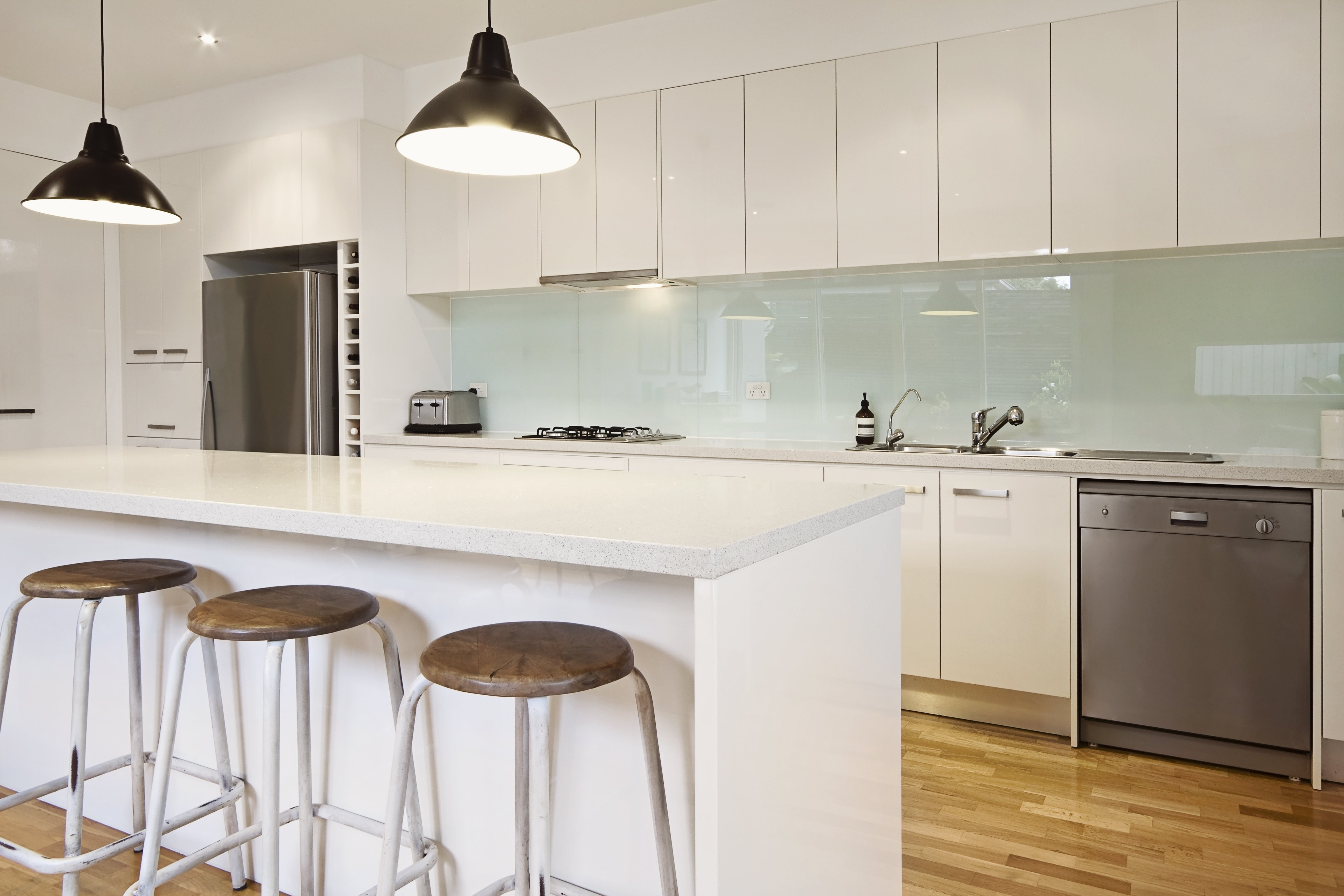 This neutral benchtop allows the subtle colour chosen for the splashback to stand out.