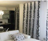 vista interna di una casa con tende e divano bianco