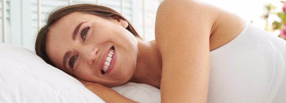 una ragazza che sorride mentre è sul letto
