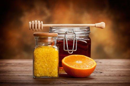 dei vasetti con dei prodotti e un'arancia tagliata a meta'