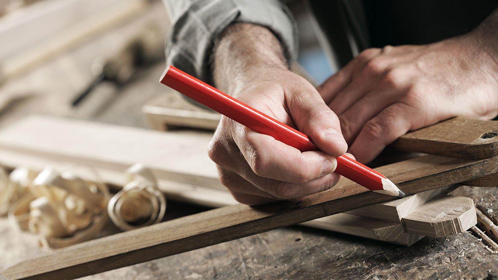 falegname con un righello per disegnare una linea su una tavola