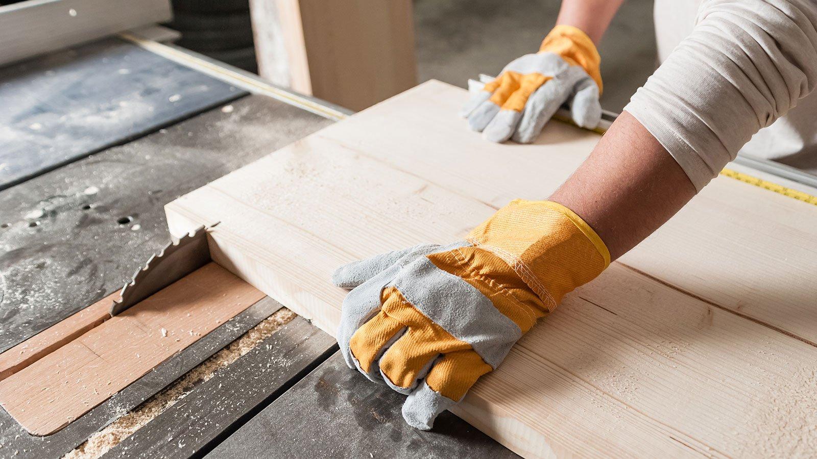Carpenter lavorando con lo strumento industriale in fabbrica di legno