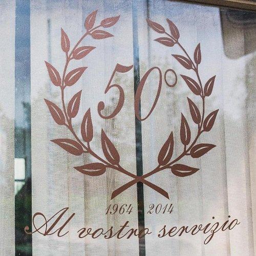 Dettaglio di una finestra dell'impresa con la corona di alloro e la commemorazione del cinquantesimo anniversario