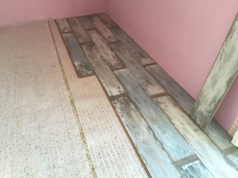 listelle di legno in parte posizionate e in parte non per realizzare un pavimento in parquet