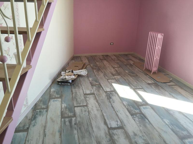 parquet in legno sfumato in un sottoscala con pareti rosa e un termosifone