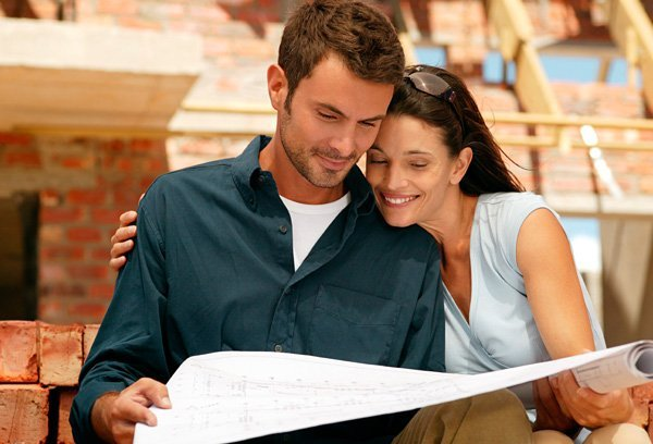 young couple looking at plans of jac home